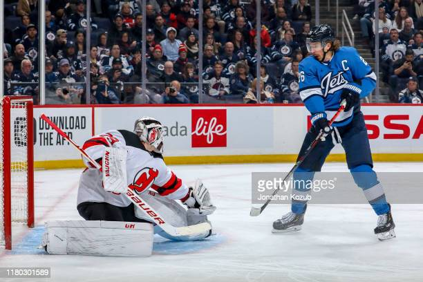 Blake Wheeler of the Winnipeg Jets watches as goaltender Mackenzie Blackwood of the New Jersey Devils makes a glove save during second period action...