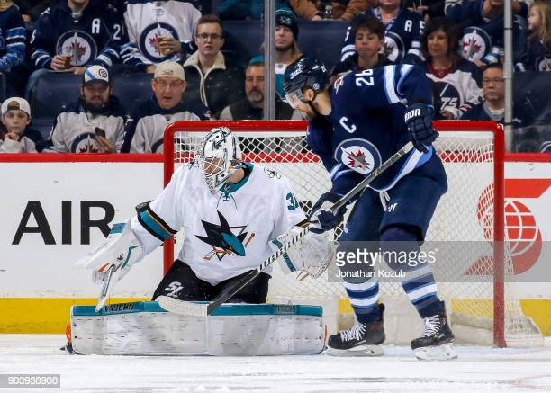Blake Wheeler of the Winnipeg Jets watches as goaltender Martin Jones of the San Jose Sharks deflects the puck wide of the goal during first period...