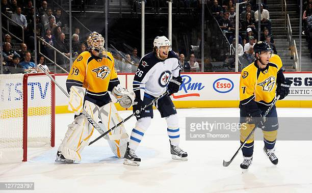 Blake Wheeler of the Winnipeg Jets watches play between Anders Lindback and Jonathon Blum of the Nashville Predators in first period action during...