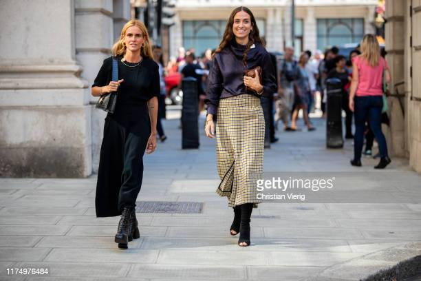 Blanca Miró Scrimieri is seen wearing black dress and Erika Boldrin wearing blouse, checkered skirt outside Victoria Beckham during London Fashion...