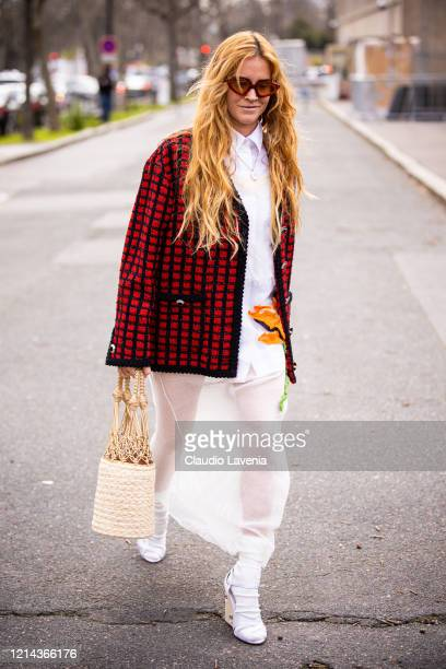 Blanca Miro Scrimieri, wearing a white shirt, white decorated long dress, red and black checked jacket, rattan bag, white socks and white sandals, is...
