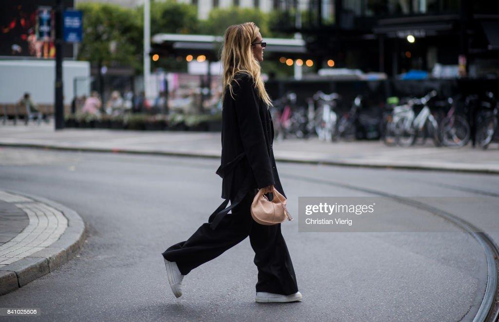 Blanca Miro Scrimieri wearing black coat and wide leg pants outside Rodebjer on August 30, 2017 in Stockholm, Sweden.