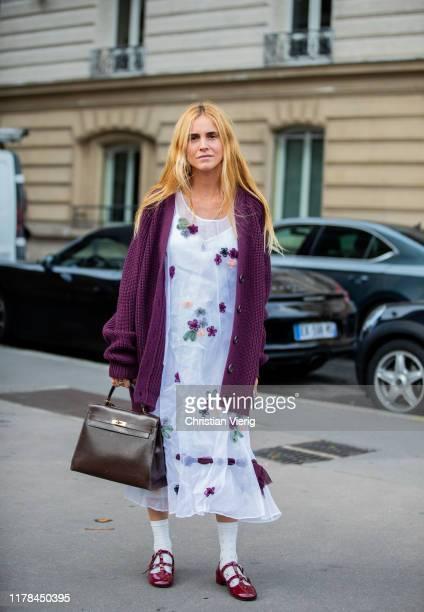 Blanca Miro seen wearing white dress with print, purple cardigan outside Miu Miu during Paris Fashion Week Womenswear Spring Summer 2020 on October...