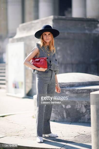 Blanca Miro wears a black hat, a gray sleeveless jacket, a red bag, gray pants, white shoes, outside Maison Margiela, during Paris Fashion Week...