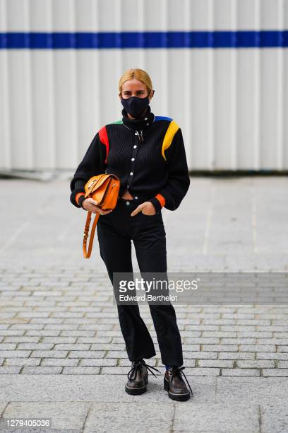Blanca Miro wears a black jacket with colored stripes on the shoulders, an orange Vuitton bag, black pants, brown leather Vuitton monogram shoes,...