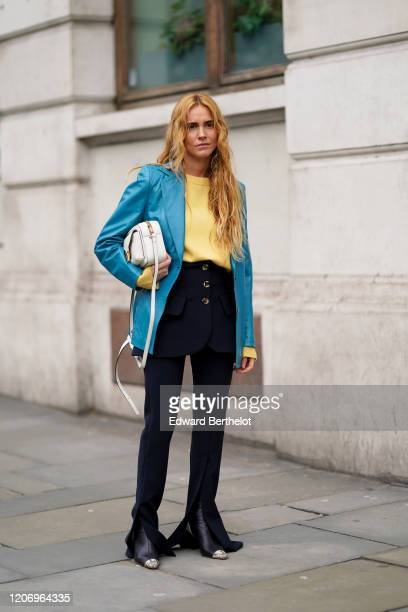 Blanca Miro wears a blue blazer jacket, a yellow pullover, a dark short skirt with buttons, dark flared pants, pointy boots, a white bag, during...