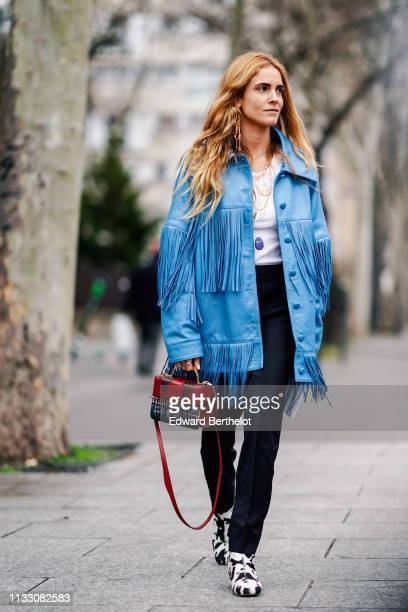 Blanca Miro wears a blue fringed jacket a red and multicolor tweed bag black pants black and white shoes with animal print outside Nina Ricci during...