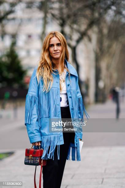 Blanca Miro wears a blue fringed jacket a red and multicolor tweed bag black pants outside Nina Ricci during Paris Fashion Week Womenswear...