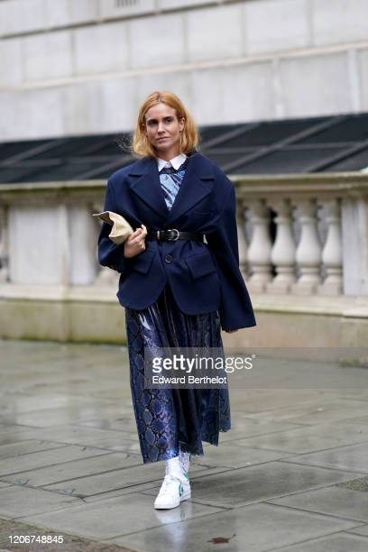 Blanca Miro wears a blue oversized blazer jacket a belt a white shirt a blue snake pattern printed pleated dress white sneakers a bag during London...