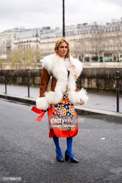 Blanca Miro wears a brown coat with white fluffy parts, a red an yellow floral print skirt, a metallic bag, blue tights, black leather pointy shoes,...