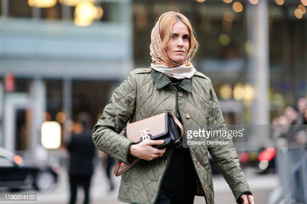 Blanca Miro wears a Burberry scarf over the head, a green puffer jacket, a Burberry bag, black pants, outside Burberry, during London Fashion Week...