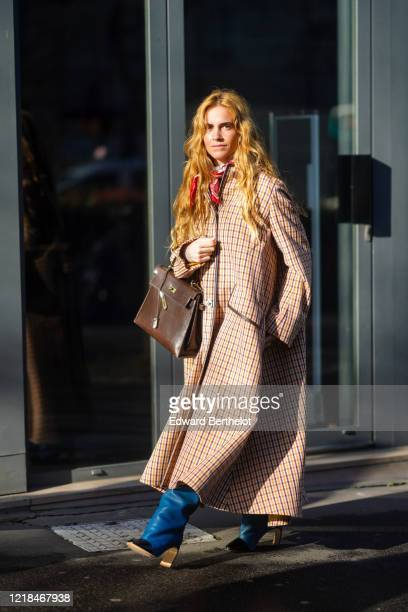 Blanca Miro wears a checked long coat, a red scarf, a brown leather Hermes bag, blue leather boots, outside Lanvin, during Paris Fashion Week -...