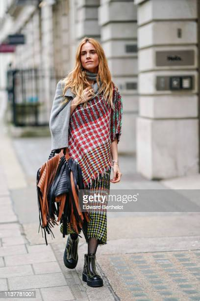Blanca Miro wears a grey scarf a colorful checkered sarilike fringed dress a fringed black and tancolor bag yellow stitched platform black boots...