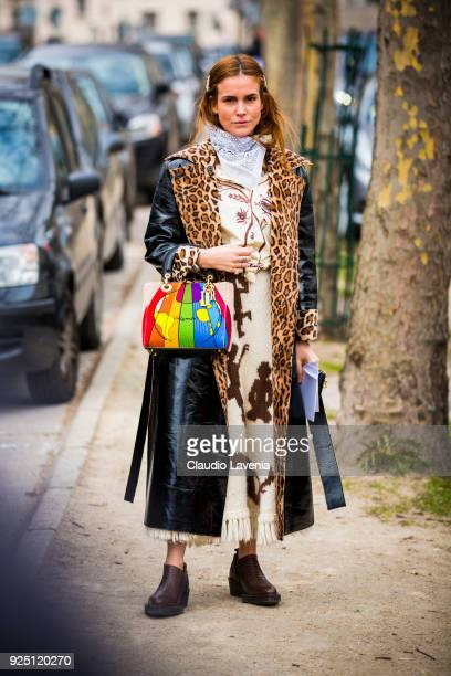 Blanca Miro wears a long black trench with animalier collar and a colored Dior bag in the streets of Paris after the Dior show during Paris Fashion...
