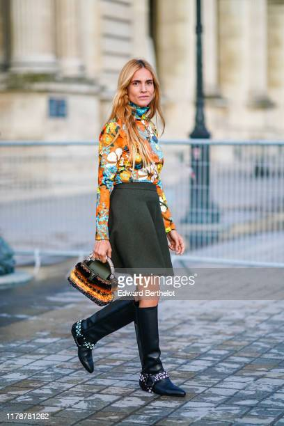 Blanca Miro wears a multicolor floral print turtleneck top, a skirt, a Vuitton orange and black striped fluffy bag, black studded leather high boots,...