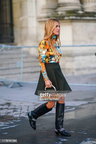 Blanca Miro wears a multicolor floral print turtleneck top a skirt a Vuitton orange and black striped fluffy bag black studded leather high boots...