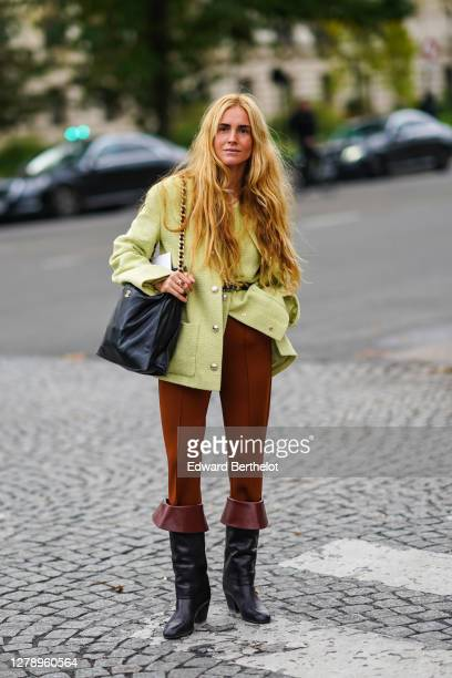 Blanca Miro wears a pale green tweed jacket with silver metallic buttons, a black leather Chanel bag, brown pants, black leather boots, outside...