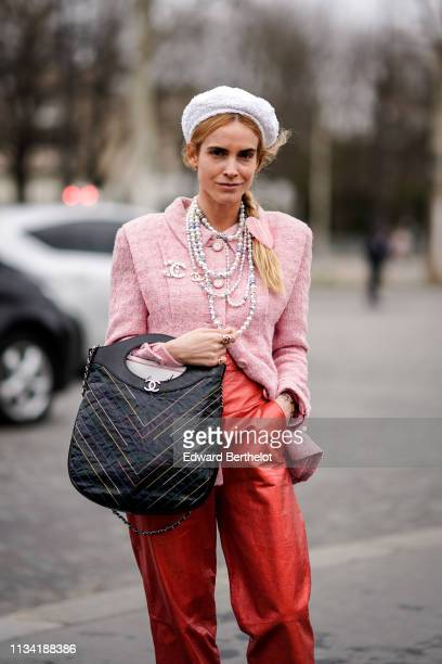 Blanca Miro wears a white beret hat, a pink tweed jacket, a Chanel brooch, a necklace, red leather pants, a black Chanel bag, outside Chanel, during...