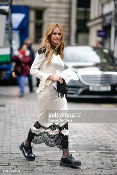 Blanca Miro wears a white dress with black lace Boredom black shoes during London Fashion Week February 2019 on February 18 2019 in London England