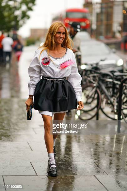 Blanca Miro wears a white ruffled shirt with bejeweled and pink plastic parts, a black skirt, white socks, black shoes, during London Fashion Week...