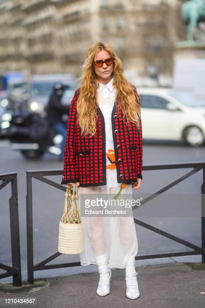 Blanca Miro wears sunglasses a black and red checked jacketa white shirt a white mesh skirt a woven bag with a net boots outside Miu Miu during Paris...
