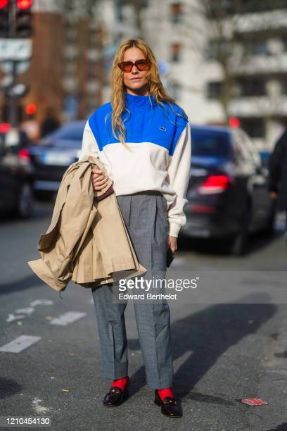 Blanca Miro wears sunglasses, a blue and white Lacoste jacket, gray pants, red socks, black leather shoes, holds a trench coat, outside Lacoste,...