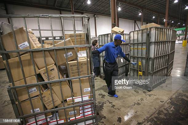 Blanch DeJesus and Darnell Horton unload mail from a truck at the United States Postal Service Chicago Logistics and Distribution Center on December...