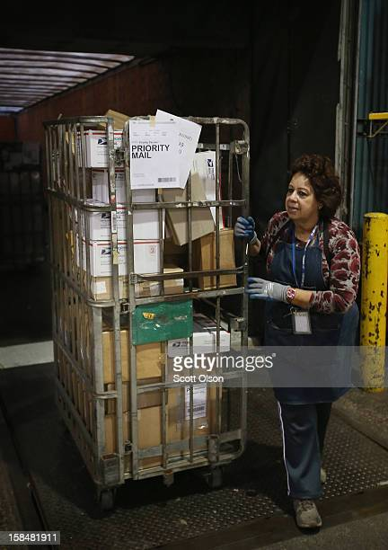Blanch DeJesus unloads mail from a truck at the United States Postal Service Chicago Logistics and Distribution Center on December 17 2012 in Elk...
