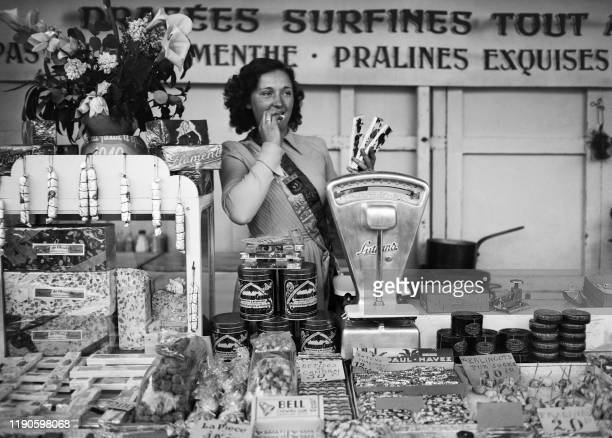 Blanche Fleur a 18 year old confectioner eats candies on April 22 1949 at the Foire du Trône in Paris after being elected Esmeralda of 1949 by the...