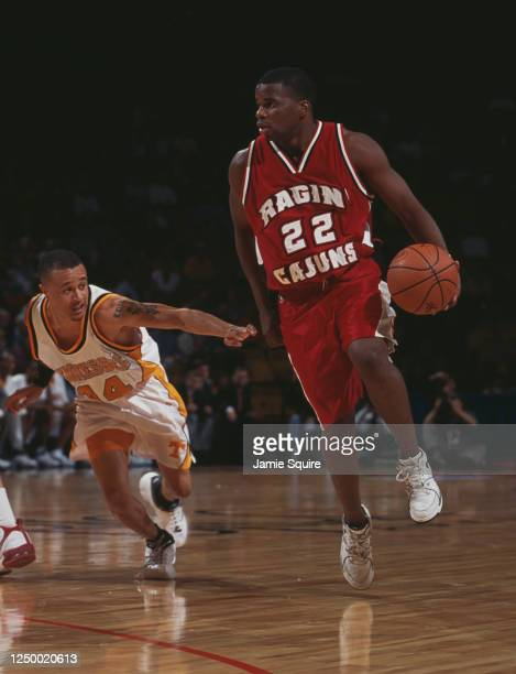 Blane Harmon, Guard for the Louisiana-Lafayette Ragin' Cajuns dribbles the ball past Tony Harris of the University of Tennessee Volunteers during...