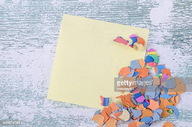 Blank adhesive note and confetti on wood