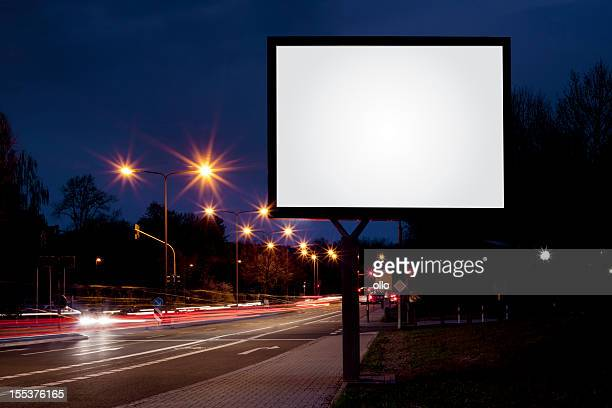Blank advertising billboard on city street at night