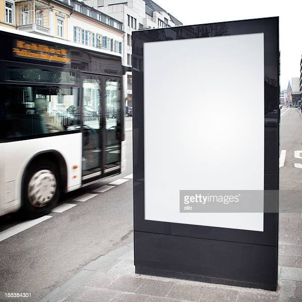 Blank advertising billboard on city street, bus passes