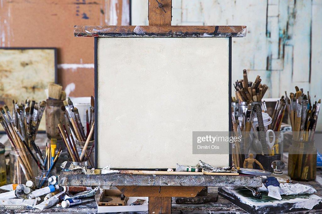 Blank art canvas in mess artist's studio : Stock Photo