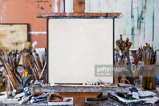 blank art canvas in mess artist's studio - easel stock pictures, royalty-free photos & images