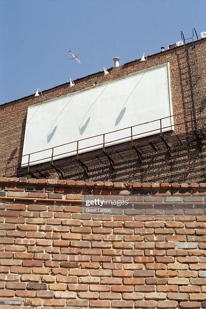 A Blank Billboard Hanging From The Side Of Brick Building Stock Photo