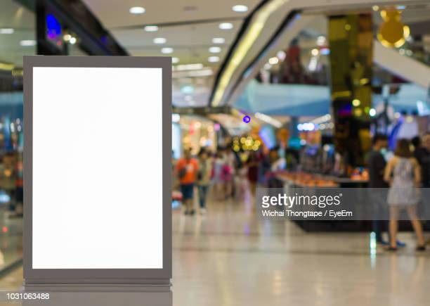 blank billboard in illuminated shopping mall - shopping mall stock pictures, royalty-free photos & images