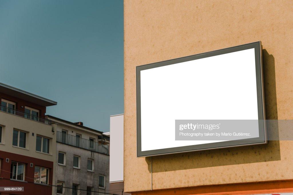 Blank billboard on building facade : Stock Photo