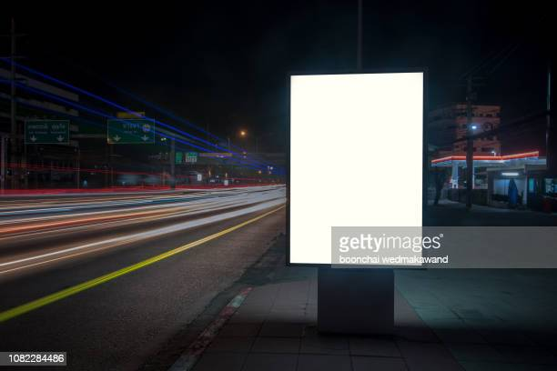 blank billboard on city street at night. outdoor advertising - poster stock pictures, royalty-free photos & images