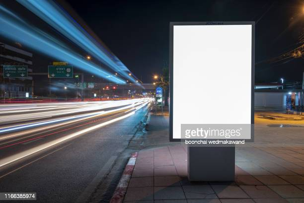 blank billboard on city street at night. outdoor advertising - placard stock pictures, royalty-free photos & images