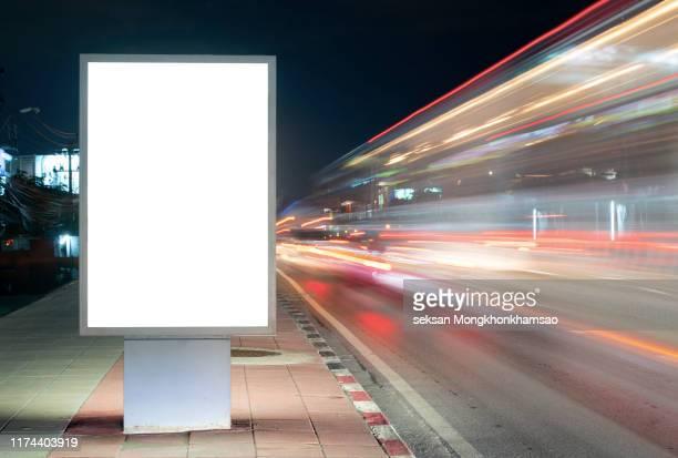blank billboard on city street at night. outdoor advertising - auslage stock-fotos und bilder