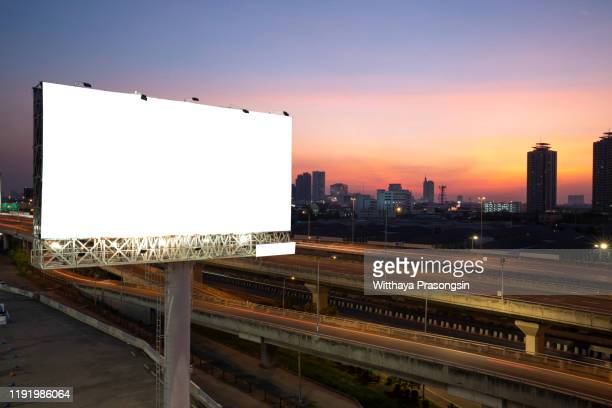blank billboard on the highway during the twilight with city background with clipping path on screen.- can be used for display your products or promotional - road sign board stock pictures, royalty-free photos & images
