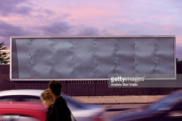 blank billboard with passing pedestrians
