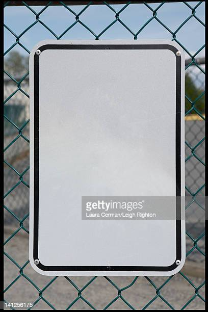 Blank black and white sign on a fence.