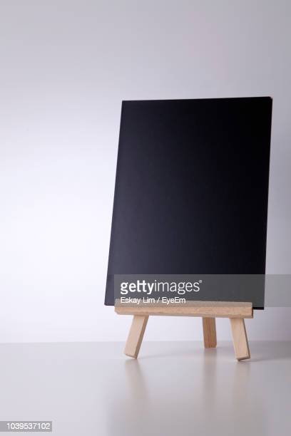 blank blackboard on table against white background - easel stock pictures, royalty-free photos & images