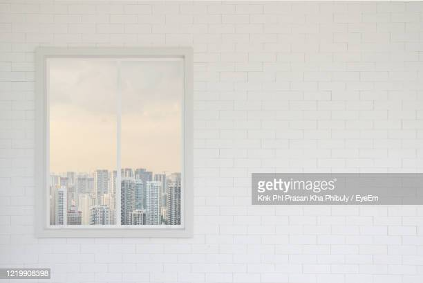 blank brick wall in white and modern window with skyscraper view - window frame stock pictures, royalty-free photos & images