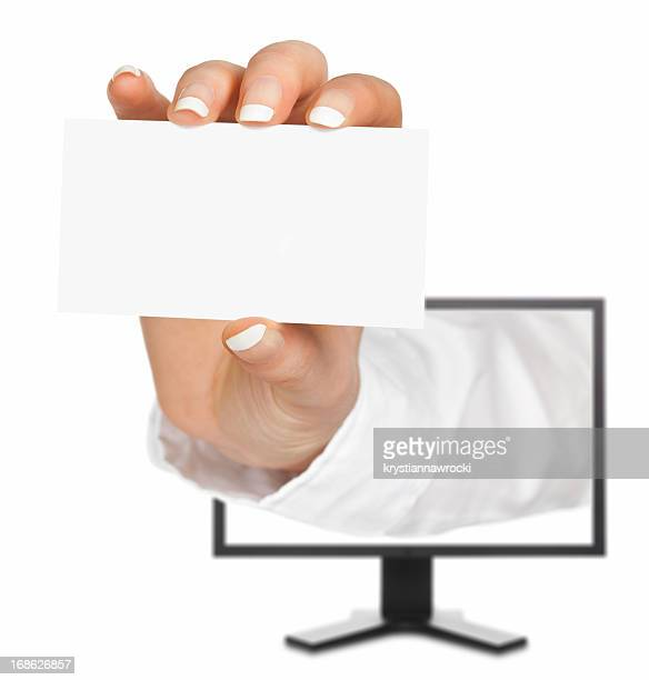 Blank business card in a hand emerges from monitor screen