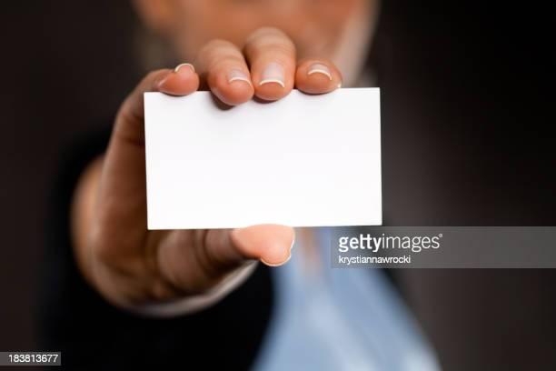 Blank business card in businesswoman's hand on dark background