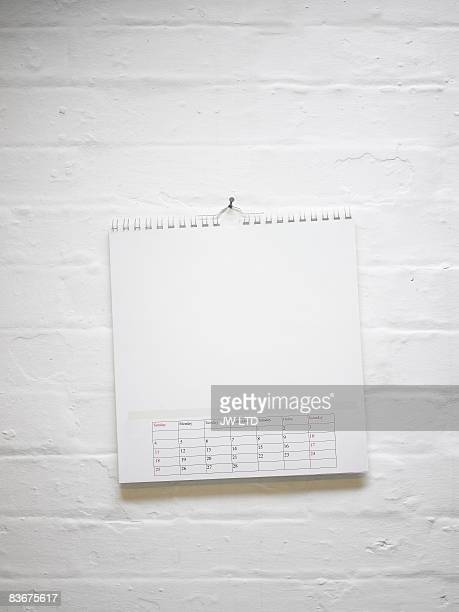 Blank calendar hanging on white brick wall