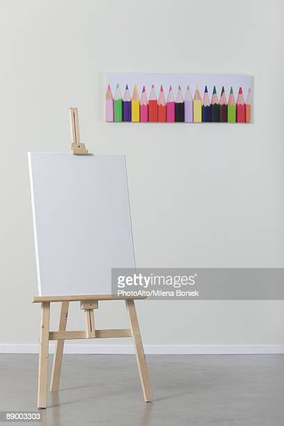 Blank canvas on easel, poster of colored pencils in background